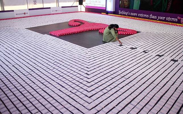 An Indian woman arranging sanitary napkins on Jan. 10, 2019 during an attempt to enter the Guinness World Record by creating the longest line of sanitary pads at the 62nd edition of 'All India Congress of Obstetrics and Gynaecology (AICOG)' in Bangalore. The Scottish parliament on Tuesday is due to approve plans to make sanitary products freely available to all women - the first nation in the world to do so.