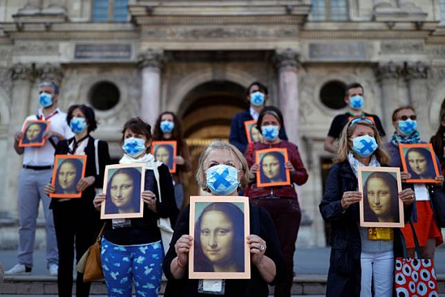 Paris tour guides hold posters depicting Mona Lisa painting by artist Leonardo da Vinci during an action at Le Louvre museum courtyard to warn on their working conditions as the museum reopens its doors to the public after almost 4-month closure due to the coronavirus disease (COVID-19) outbreak in France, on July 6, 2020.