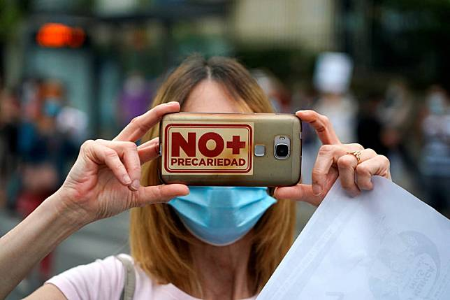 A woman holds a phone with a sign reading 'No more precariousness' as staff members of Nino Jesus hospital protest against the privatization of public health, amid the COVID-19 outbreak in Madrid, Spain on Monday.