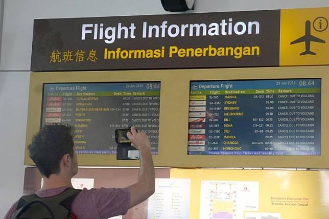 A traveler records the flight delays at Ngurah Rai airport in Denpasar, Bali.