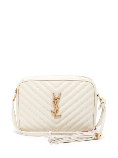 Saint Laurent - Updated in chic cream for the new season, Saint Laurent's Lou bag is crafted in Italy from the house's hallmark quilted leather. It's shaped to a classic satchel silhouette with tonal piped edges, a hanging tassel and centred by the label's gold-tone Cassandre logo. Carry it as the understated complement to tan tailoring.