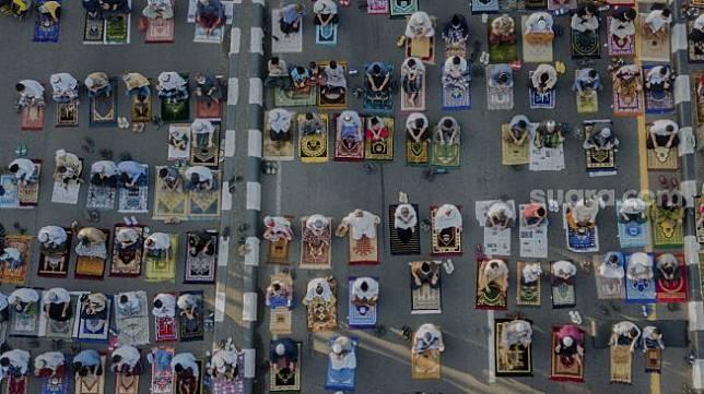 Foto aeria lumat Islam melaksanakan shalat Idul Fitri 1 Syawal 1441 Hijriah secara berjamaah di ruas Jalan Jenderal Sudirman, Kranji, Bekasi, Jawa Barat, Minggu (24/5). [Suara.com/Angga Budhiyanto]