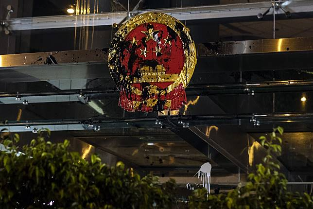 A defaced Chinese emblem is displayed outside the Liaison Office of the Central People's Government during a protest in Hong Kong. Photographer: Justin Chin/Bloomberg