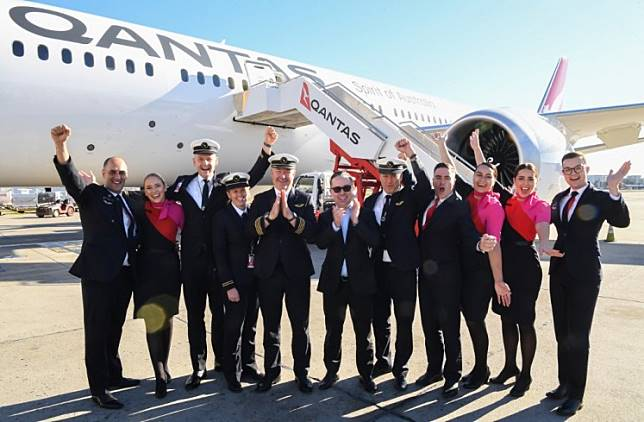 In this handout photo from Qantas shows Qantas Group CEO Alan Joyce (C) and crew celebrating in front of a Qantas Boeing 787 Dreamliner plane after arriving at Sydney international airport after completing a non-stop test flight from New York to Sydney on October 20, 2019. The Qantas Boeing 787 completed the flight, non-stop New York to Sydney in 19 hours and 15 minutes.