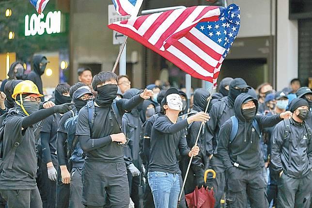 大批參加遊行的黑衣示威者揮舞美國國旗。(美聯社圖片)
