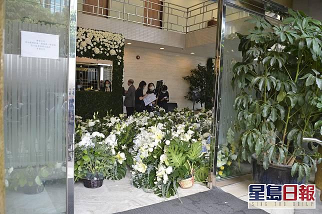 殯儀館的地面大堂牆上以白玫瑰及綠色植物作佈置。