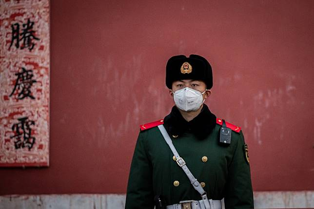 A paramilitary police officer wearing a protective facemask to help stop the spread of a deadly SARS-like virus, which originated in the central city of Wuhan, stands guard at the exit of the Forbidden City in Beijing on January 25, 2020.