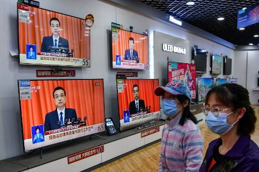 People walk past televisions broadcasting live coverage from Beijing of Chinese Premier Li Keqiang delivering his speech during the opening session of the National People's Congress (NPC), at a shopping mall in Yantai in China's eastern Shandong province on May 22, 2020. China moved to impose stringent new security laws on restive Hong Kong as its coronavirus-delayed parliamentary session opened on May 22 with a warning from Premier Li Keqiang of the 'immense' challenges facing the world's second-largest economy.