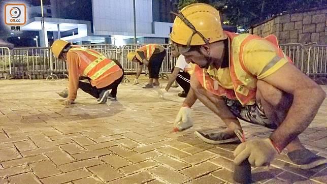 工人在地磚之間的罅隙塗上難聞的膠水。(朱先儒攝)