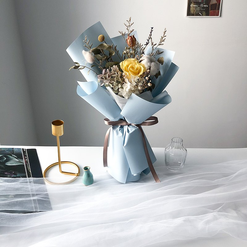 黃玫瑰搭配藍色包裝紙,如黃澄澄的冬日曙光映照在太平洋上。