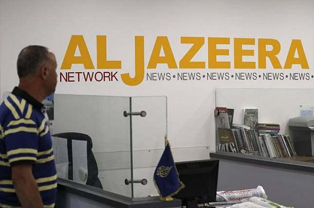 Employees of Qatar based news network and TV channel Al-Jazeera are seen at their Jerusalem office on July 31, 2017.Malaysian police on Monday opened an investigation into a documentary by news broadcaster Al Jazeera on the country's arrests of undocumented migrants, which authorities have accused of being an attempt to tarnish Malaysia's image.