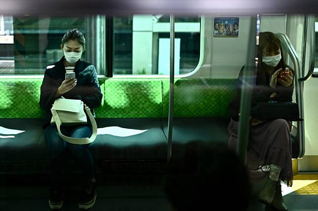 Women use their phones on the Yamanote Line train in Tokyo on Wednesday, on the first day of the state of emergency. - Japan on April 7 declared a month-long state of emergency over a spike in coronavirus cases, ramping up efforts to contain infections but stopping short of the strict lockdowns seen in other parts of the world.