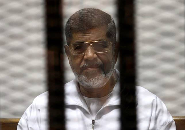 Ousted Egyptian President Mohamed Mursi is seen behind bars during his trial at a court in Cairo May 8, 2014.