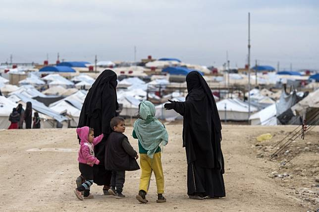 Displaced Syrian women and a children walk toward tents at the Internally Displaced Persons (IDP) camp of al-Hol in al-Hasakeh governorate in northeastern Syria,on February 7, 2019.
