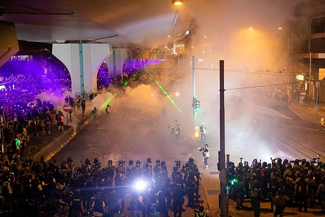Riot police deploy tear gas to disperse demonstraters. Photographer: Kyle Lam/Bloomberg
