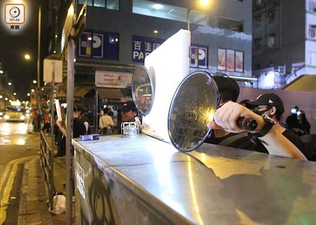 有示威者用鏡反射警方的強光。(袁以諾攝)