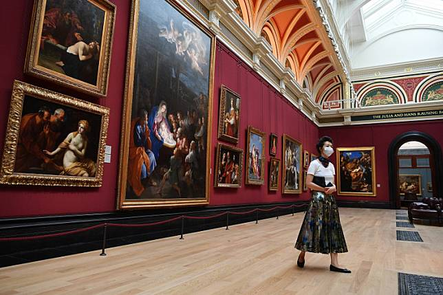 A member of staff wearing a protective face mask moves through a room inside the National Gallery on July 4, 2020, as the gallery prepares to reopen on July 8 following the easing of restrictions imposed during the novel coronavirus COVID-19 pandemic.