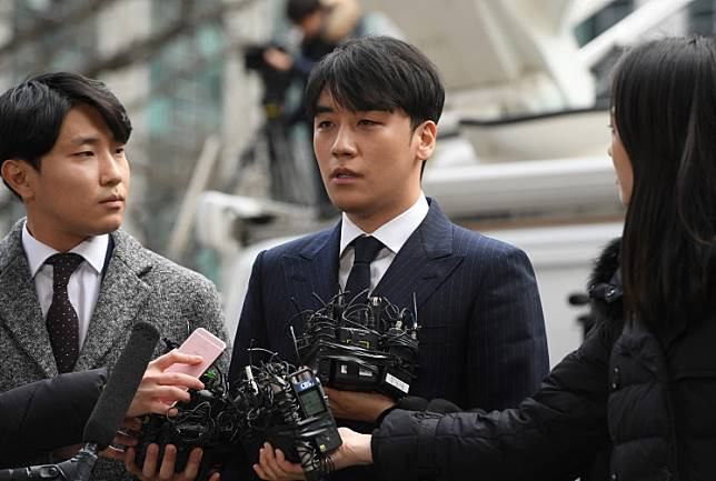 Seungri (C), a member of the K-pop boy group BIGBANG, speaks to the media as he arrives for questioning over criminal allegations at the Seoul Metropolitan Police Agency in Seoul on March 14, 2019.