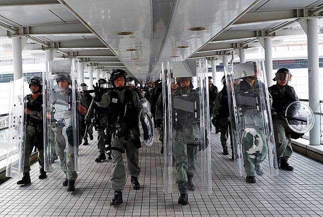 Riot police advance in Tung Chung station, in Hong Kong