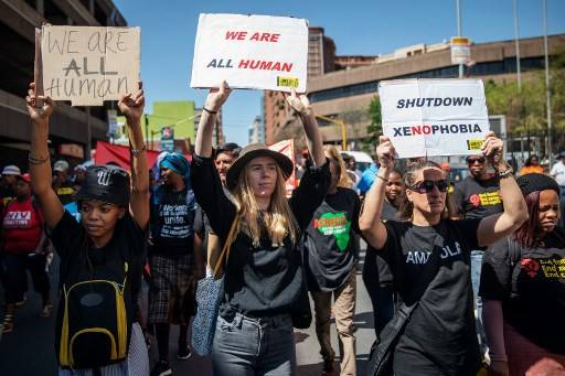 Women hold signs during a civil society groups march against the recent rise of xenophobic attacks in South Africa, on September 14, 2019, in Johannesburg's Central Business District. At least twelve people have been killed and hundreds of shops destroyed since the start of September in a surge in attacks targeting foreign-owned businesses in and around South Africa's largest city.