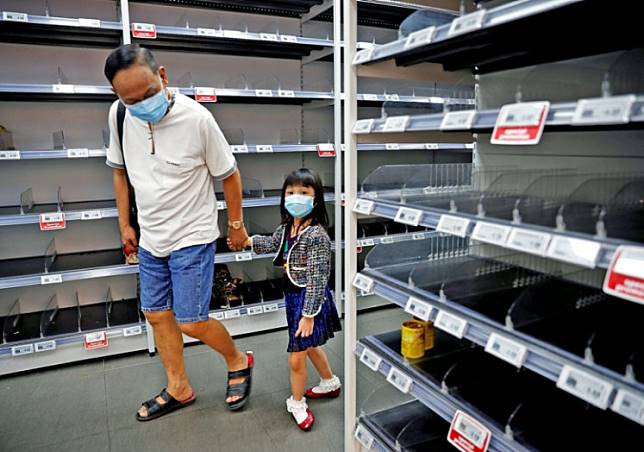 A man and a child wearing face masks look at empty shelves in a supermarket in Singapore after the government raised the coronavirus outbreak alert level to orange on Feb. 8. ASEAN member states are working together to fight the virus.