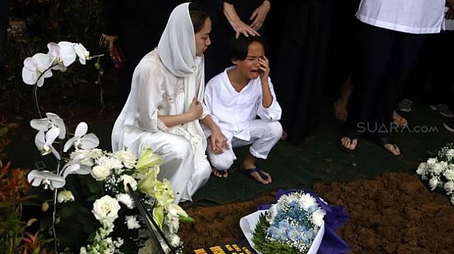 Bunga Citra Lestari memeluk anaknya Noah Sinclair yang menangis saat prosesi pemakaman Ashraf Sinclair di kompleks pemakaman San Diego Hills, Karawang, Jawa Barat, Selasa (18/2). [Suara.com/Angga Budhiyanto]