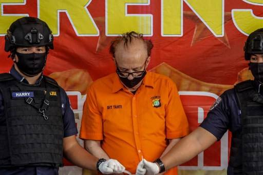 Indonesian police guard a Frenchman, Francois Camille Abello (center), 65, during a press conference in Jakarta, on July 9, 2020, after he got arrested last month at a hotel where the police found two underaged girls in his room. - A French retiree could face the death penalty in Indonesia on charges that he molested over 300 children and beat those who refused to have sex with him, authorities said on July 9.