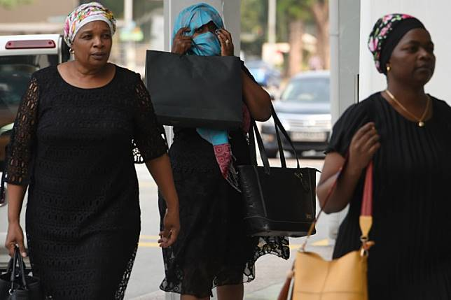 Relatives of the late former Zimbabwe president Robert Mugabe arrive at the Singapore Casket building in Singapore on September 10, 2019, where his body is currently being kept. Mugabe, a guerrilla leader who swept to power after Zimbabwe's independence from Britain and went on to rule for 37 years until he was ousted in 2017, died on September 6, aged 95.