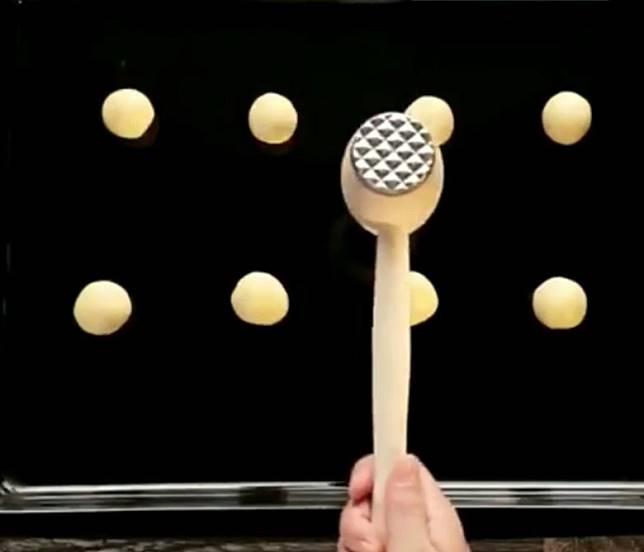 將肉鎚的一邊,輕力壓在搓好的圓球狀麵糰。(互聯網)