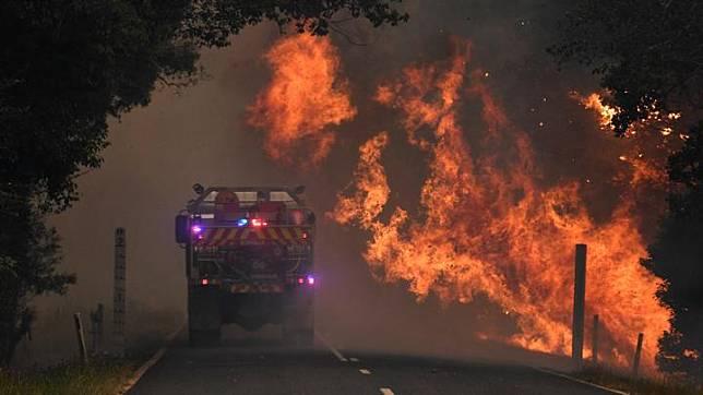 Sebuah truk pemadam terlihat di dekat api dalam kebakaran lahan di Nana Glen, dekat Coffs Harbour, Australia, 12 November 2019. AAP Image/Dan Peled/via REUTERS