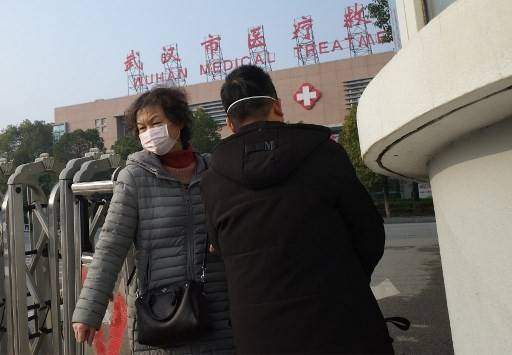 A woman (left) leaves the Wuhan Medical Treatment Center, where a man who died from a respiratory illness was confined, in the city of Wuhan, Hubei province, on Jan. 12, 2020. A 61-year-old man has become the first person to die in China from a respiratory illness believed caused by a new virus from the same family as SARS, which claimed hundreds of lives more than a decade ago, authorities said.