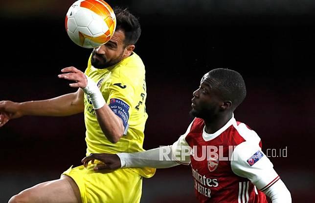 Pemain Villareal Mario Gaspar (kiri) dan pemain Arsenal Nicolas Pepe berebut bola pada pertandingan sepak bola leg kedua semifinal Liga Europa antara Arsenal dan Villarreal di Stadion Emirates di London, Inggris, Jumat (7/5) dini hari WIB.