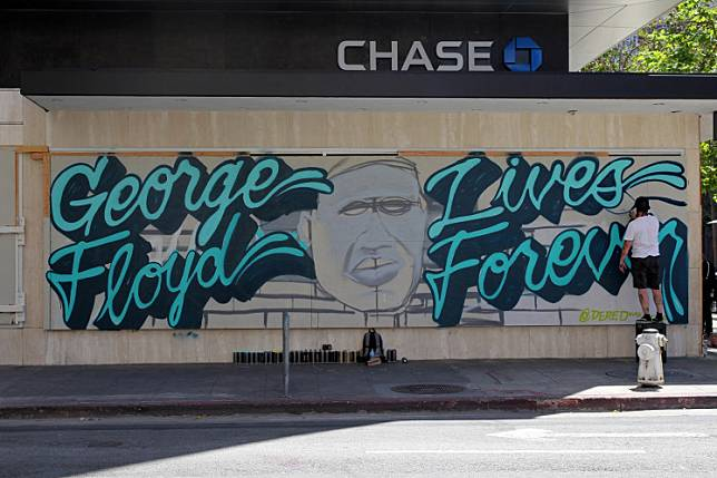 Local artist 'Shawn' paints a mural in memory of for George Floyd, who died in Minneapolis police custody, in downtown Oakland, California, US, on June 3.