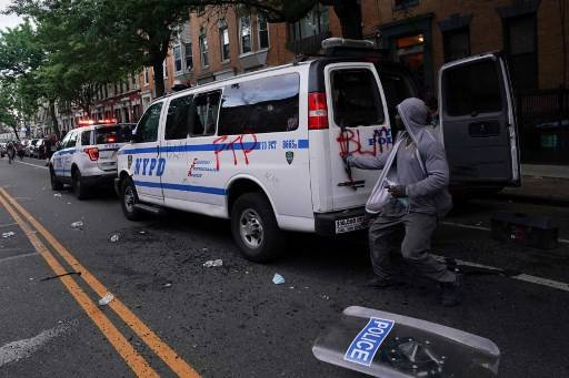 A man loots an NYPD police van  during a demonstration against the killing of George Floyd by Minneapolis police on Memorial Day on May 30, 2020 in the Borough of Brooklyn in New York .New York's mayor Bill de Blasio on Monday declared a city curfew from 11:00 pm to 5:00 am, as anti-racism protests grip the United States with regular outbreaks of violence and looting.