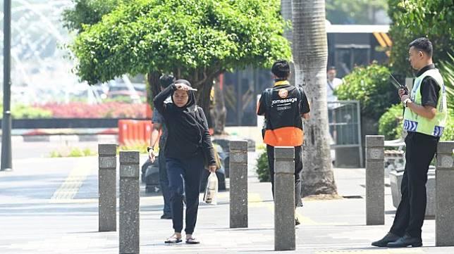 Warga menghalau sinar matahari dengan tangannya saat melakukan aktivitas di kawasan Bundaran Hotel Indonesia, Jakarta, Selasa (22/10). [ANTARA FOTO/Muhammad Adimaja]