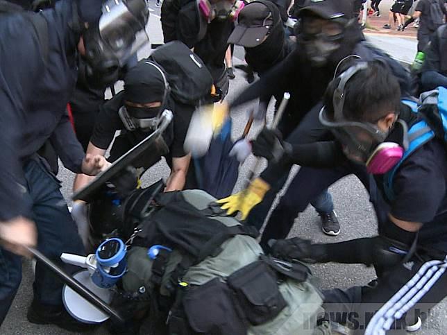 有人搶去警棍隨即揮棍打警員;另一邊有人懷疑嘗試搶去警員腰間配件,相信是配槍。(爾超軍攝)
