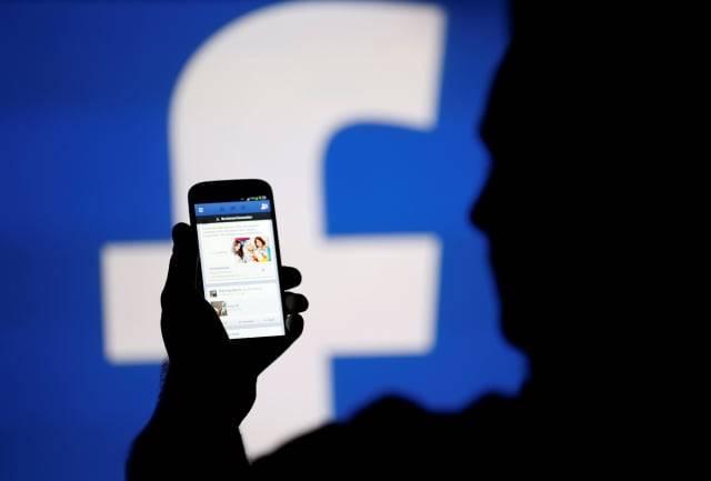 Siluet seorang pria nampak tengah memegang handphone dengan logo Facebook di belakang (Foto: Reuters)