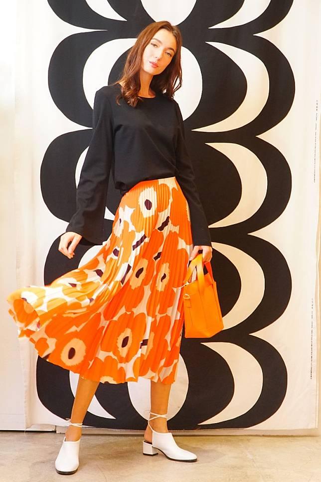 Marimekko黑色上衣、Unikko Viserys花卉圖案百褶半截裙、Milli Matkuru橙色手袋、白色尖頭鞋(莫文俊攝)