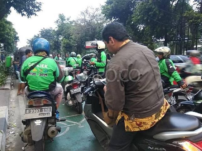 Puluhan ojek online dan bajaj parkir di jalur sepeda Jalan Melawai Raya, Jakarta Selatan, Jumat, 13 Juli 2018. Tempo/Imam Hamdi