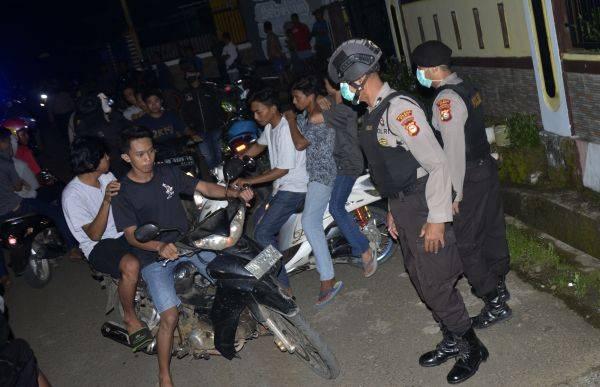 Petugas kepolisian membubarkan warga yang berkumpul di pinggir jalan