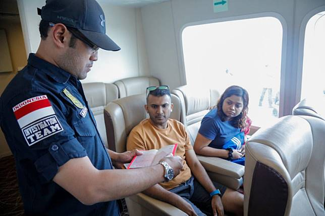 An immigration officer checks the passport of two foreigners.