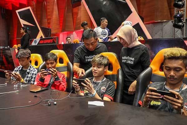 Direktur Utama Telkom Ririek Adriansyah (ketiga dari kiri) dan Direktur Consumer Service Telkom Siti Choiriana (kedua dari kanan) bebincang dengan peserta turnamen saat grand final IndiHome eSports League Games di Jakarta, Jumat (6/12).