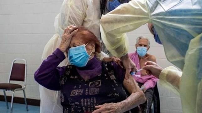 Perawat dari Rumah Sakit Humber River memberikan vaksin COVID-19 buatan Pfizer/BionTech kepada seorang wanita lansia, Maria DiStefano, di St Fidelis Parish, di Toronto, Ontario, Kanada, Rabu, 17 Maret 2021.