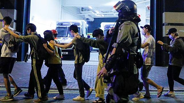 Protesters are escorted by police out of the campus of Hong Kong Polytechnic University (PolyU) during clashes with police in Hong Kong, China November 18, 2019. REUTERS/Thomas Peter
