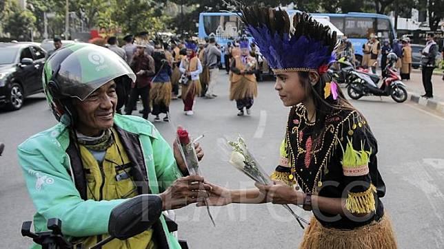 Ikatan Mahasiswa Papua mengadakan aksi membagikan bunga kepada masyarakat di Kawasan Patung Arjuna Wijaya, Jakarta, Kamis, 19 September 2019.Aksi ini dalam rangka menjaga persatuan rakyat Indonesia dengan mengangkat tema : `Sa Papua Sa Indonesia`. TEMPO/Muhammad Hidayat