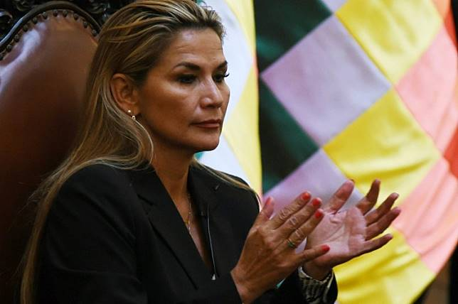Bolivia's interim president, Jeanine Anez applauds after taking oath to the military command during her first day in power, at the Quemado presidential palace in La Paz, on November 13, 2019. Anez, who declared herself interim president before her claim was endorsed by the constitutional court, arguing that her succession was necessitated by the resignations of those above her in the government hierarchy, will try to fill the power vacuum left by Evo Morales's abrupt resignation, as the former leader denounced what he described as a