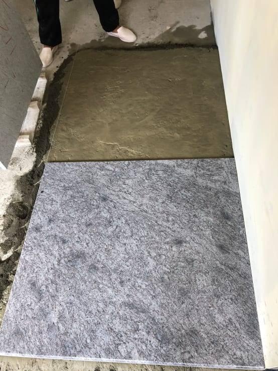 在水泥砂基底上,再淋上一層水泥漿做為黏著劑用,之後蓋上石材依據水線調整高程及縫線。