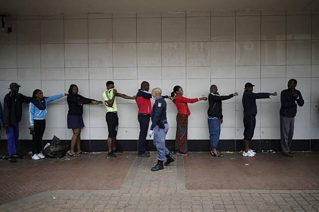 A member of the South African Police Service (SAPS) enforces social distancing as he makes shoppers hold their hands out in front of them to ensure that they are at least one metre apart from one another while they queue outside a supermarket in Yeoville, Johannesburg, on Saturday. South Africa's confirmed cases of the coronavirus increased by 93 to 1,280 people on Sunday and the death toll doubled to two.