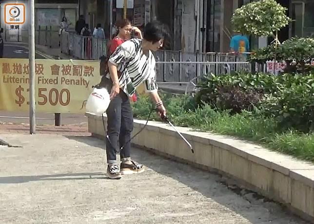 張錫容自行向清潔公司借用工具在餵鴿黑點噴灑驅鴿劑。