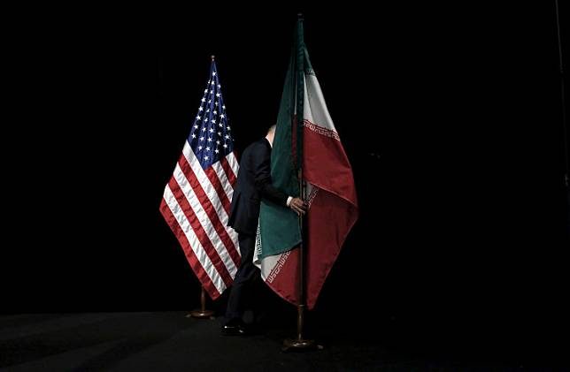 A staff member removes the Iranian flag from the stage after a group picture with foreign ministers and representatives of the US, Iran, China, Russia, Britain, Germany, France and the European Union during Iran nuclear talks at the Vienna International Center in Vienna, Austria, July 14, 2015.A US Navy veteran who said he contracted the coronavirus while detained in Iran since 2018 was freed on Thursday as part of a deal in which the United States allowed an Iranian-American physician to visit Iran, his lawyer and a US official said.